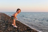 Happy smiling 2 years boy standing on the pebbles beach at sunse — Stock Photo