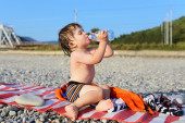 Lovely 2 years boy drinking water on the pebbles beach — Stock Photo