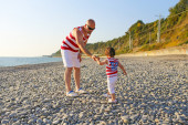 Father and 2 years son in similar clothes walk on the seaside — Stock Photo