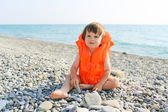 2 years child in life-saving jacket sitting on the seaside — Стоковое фото