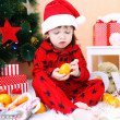 Lovely little boy in Santa hat with tangerine sits near Christma — Stock Photo #60279845