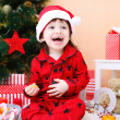 Portrait of happy little boy in Santa hat near Christmas tree — Stock Photo #60279857