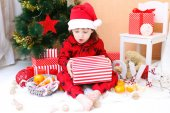 Happy little boy in Santa hat with present — Stockfoto
