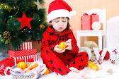 Lovely little boy in Santa hat with tangerine sits near Christma — Stock Photo