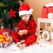 Lovely little boy with tangerine sits near Christmas tree — Stock Photo #60326163