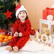 Lovely little boy in Santa hat with lollipop and presents sits n — Stock Photo #60326183