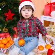Little boy in Santa hat with tangerine sits near Christmas tree — Stock Photo #60523125