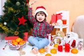 Happy 2 years boy in Santa hat sits near Christmas tree — Stock Photo