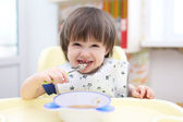 Funny 2 years boy eating soup — Stock Photo