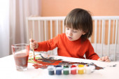 Lovely 2 years boy with brush and gouache paints at home — Stock Photo
