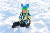 Little child sitting on the snow in winter outdoors — Stock Photo