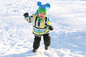Smiling happy toddler running in winter outdoors — Stock Photo