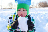 Lovely 2 years toddler boy eating snow — Stock Photo