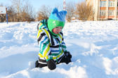Little child plays sitting on the snow in winter  — Stock Photo