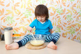 Little boy cooks sitting on a table — Stock Photo