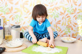 2 years boy flattening dough sitting on a table — Stock Photo