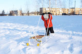 2 years child in orange jacket with sledge in winter — Stock Photo