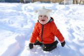 Little child in orange jacket in winter — Stock Photo