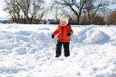 Little child in orange jacket running in winter — Stock Photo