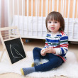 2 years toddler paints on the blackboard with chalk at home — Stock Photo #65979235