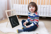 2 years toddler paints on the blackboard — Stock Photo
