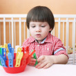 Постер, плакат: 2 years boy plays with clothes pins