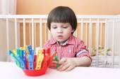 2 years boy plays with clothes pins — Stok fotoğraf