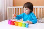 Little child sorts details by color — Stock Photo