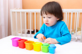 Lovely 2 years boy sorts details by color — Stock Photo