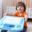Nice 2 years child shows his drawing on magnetic tablet — Stock Photo #70188435