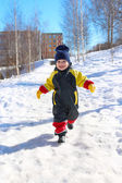 2 years child in overall running in winter — Stock Photo