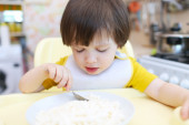 Little boy eating quark with sour cream on kitchen — Stock Photo