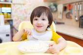 Smiling little boy eats quark with sour cream — Stock Photo