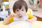 Nice little child eats quark  — Stock Photo