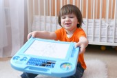 Nice 2 years child shows his drawing on magnetic tablet — Stock Photo