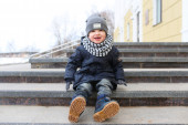 Happy fashionably dressed little boy sitting on stairs outdoors  — Stock Photo