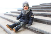 Fashionably dressed little boy sitting on stairs outdoors in spr — Stock Photo
