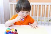 Portrait of lovely 2 years boy paints with wax pencils — Stock Photo