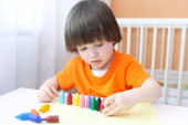 Little boy playing with wax pencils — Stock Photo