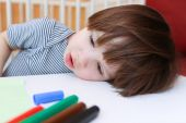 Tired little boy with felt pens rest his head on a table — Stock Photo