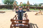 Cute little boy plays on wooden playpit — Stock Photo