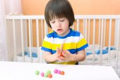 Little child (2 years) modelling playdough balls at home — Foto Stock