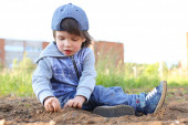Cute 2 years boy plays with sand outdoors in summer — Stock Photo