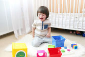 Crying little boy scatters toys — Stock Photo