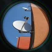 Prefab wall with satellites in objective lens — Stock Photo