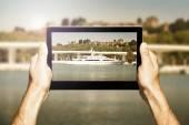 Manos sosteniendo una tableta. Tomar una foto de un yate de lujo. — Foto de Stock