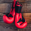 Постер, плакат: Pair of boxing gloves hanging in a rustic wooden wall Vintage tone