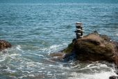 Stacked Pebble Tower being Washed by Wave — Stock Photo