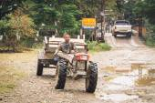 An unidentified man driving tractor on a rural road on oct 24, 2014, in Vang Vieng, Laos. Vang Vieng is a tourism-oriented town in Laos, lies on the Nam Song river. — Stock Photo