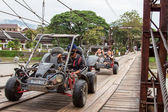An unidentified man tourist driving car on a rural road on oct 24, 2014, in Vang Vieng, Laos. Vang Vieng is a tourism-oriented town in Laos, lies on the Nam Song river. — Stock Photo